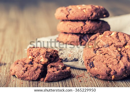 Chocolate biscuit cookies. Chocolate cookies on white linen napkin on wooden table. - stock photo