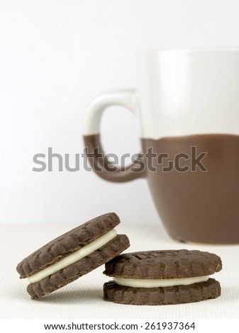 Chocolate biscuits with a milk cream filling and coffee cup - stock photo