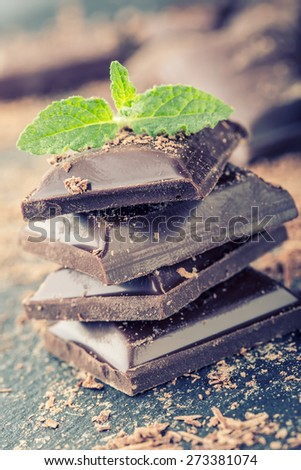Chocolate. Black chocolate. A few cubes of black chocolate with mint leaves. Chocolate slabs spilled from grated chockolate powder.   - stock photo