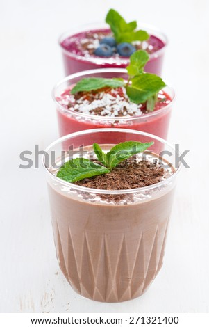 chocolate, blueberry and strawberry milkshakes in glasses, vertical, close-up, selective focus - stock photo