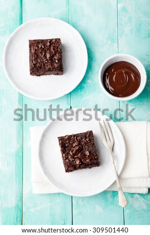 Chocolate brownie, cake on a white plate on a turquoise wooden  background - stock photo