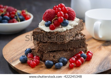 chocolate brownie cake with nuts and fresh berries on wooden board, closeup, horizontal - stock photo