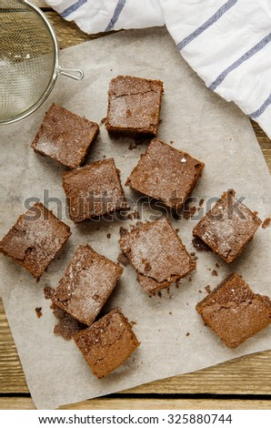 chocolate brownie diced on baking paper on a wooden table