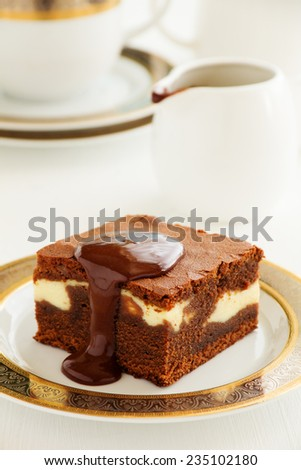 Chocolate brownie with cheese filling and chocolate sauce.