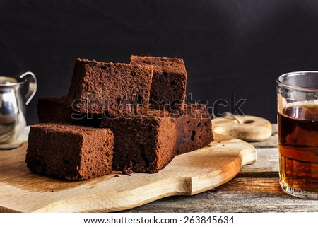 chocolate brownie with dark beer on a black background - stock photo