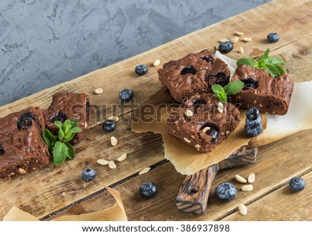 Chocolate brownie with peanuts,blueberries and mint on a wooden serving Board  - stock photo