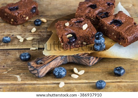 Chocolate brownie with peanuts,blueberries on a wooden serving Board  - stock photo
