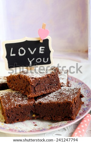 Chocolate brownies dusted with icing sugar on plate and a sign saying Love You - stock photo