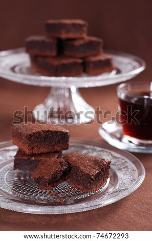 Chocolate brownies on the cake stand and cup of coffee - stock photo