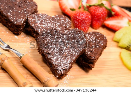 Chocolate brownies with heart shapes on the table - stock photo