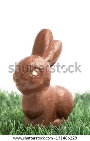 Chocolate bunny rabbit sitting on grass on white background