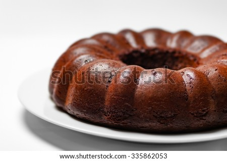 Chocolate bunt cake whole sponge on a plate white background closeup