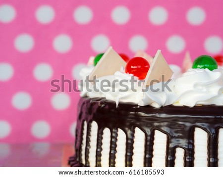 chocolate cake and whipping cream on pink background.