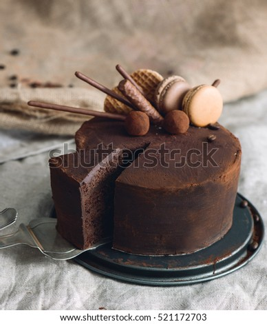 Chocolate cake covered with cocoa powder and decorated with macarons, caramel waffles, truffles and cookie sticks