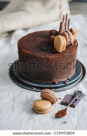 Chocolate cake covered with cocoa powder and decorated with macaroons, caramel waffles, truffles and cookie sticks