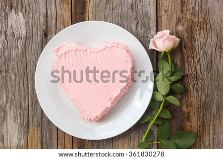 Chocolate cake decorate with pink cream butter. On wood table with pink rose. Top view.