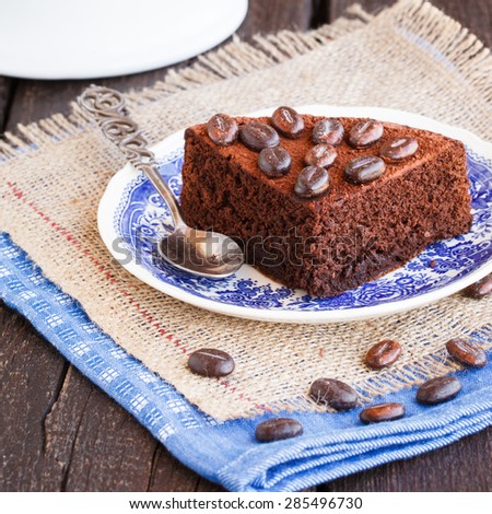 Chocolate cake, dusted with cocoa and decorated with coffee beans.selective focus - stock photo