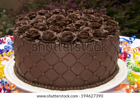 Chocolate Cake frosted and embossed with diamond impression on the sides with hand crafted Chocolate frosting roses on top - stock photo