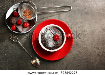 Chocolate cake in a red mug  with a cherry on top, top view - stock photo