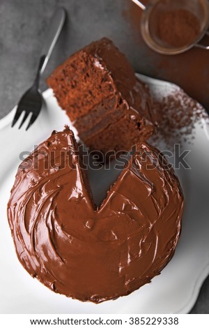 Chocolate cake on plate with a cut piece and fork and cocoa on gray background, closeup
