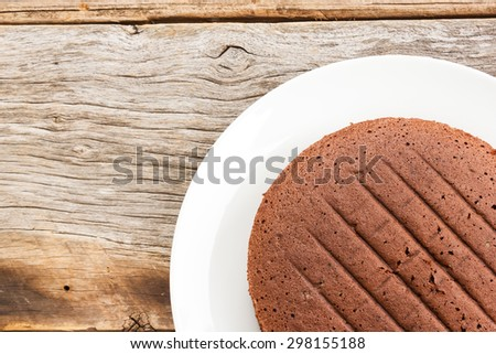 Chocolate cake on white plate. Over wooden table. Top view.