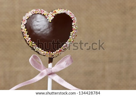 Chocolate cake pops in heart shape, lavishly decorated with colorful sprinkles - stock photo