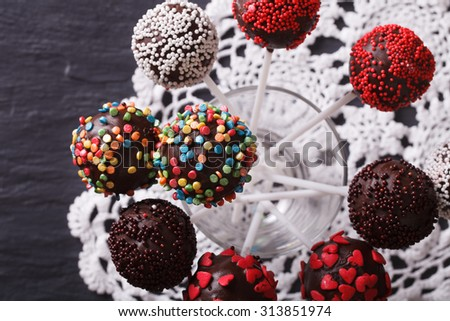 chocolate cake pops with candy sprinkles close-up on a lace doily. horizontal view from above - stock photo