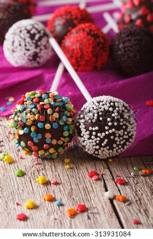 Chocolate cake pops with candy sprinkles macro on an old table. vertical