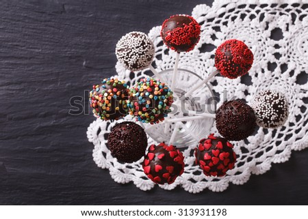 chocolate cake pops with candy sprinkles on a lace doily. horizontal view from above - stock photo
