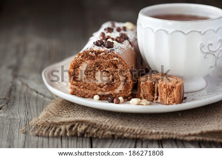 Chocolate cake roll with coffee cream and a cup of tea on a wooden background, selective focus - stock photo