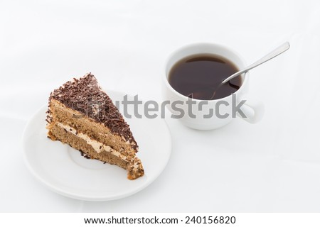 Chocolate cake slice with curl on white dish with hot drink. white background