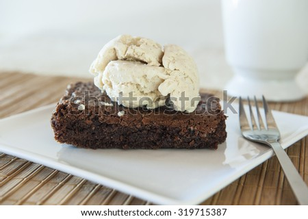 Chocolate cake with a scoop of cinnamon ice cream on top on a white plate