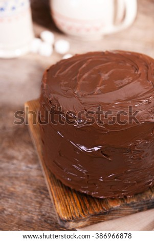 Chocolate cake with blade on a wooden boards background
