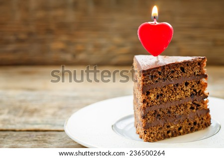 chocolate cake with candles in the shape of a heart on Valentine's day. tinting. selective focus - stock photo