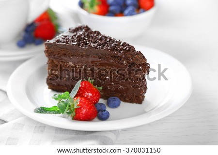 Chocolate cake with chocolate cream and fresh berries on plate, on light background - stock photo