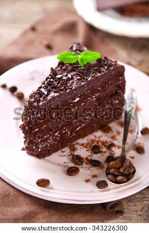 Chocolate cake with chocolate cream and fresh berries on plate, on wooden background - stock photo