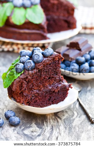 Chocolate  cake with chocolate cream and fresh blueberries and mint leaves  - stock photo