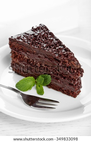 Chocolate cake with chocolate cream on plate, on light background - stock photo