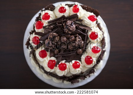 Chocolate cake with cream and cherries, from above. - stock photo