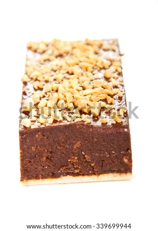 Chocolate cake with  crushed nuts topping (shallow DOF) - stock photo