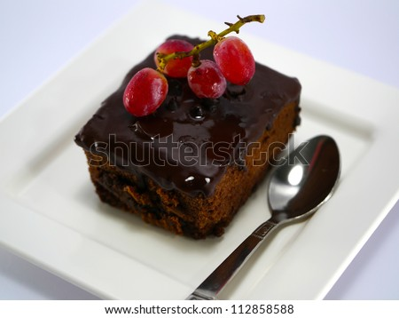 chocolate cake with fresh grapes on white isolated background - stock photo