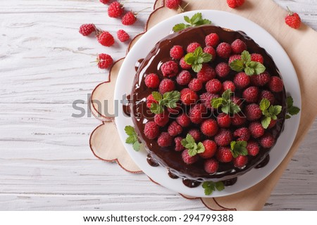 Chocolate cake with fresh raspberries and mint on the table. Horizontal top view  - stock photo