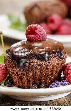 Chocolate cake with fresh raspberries on wooden table