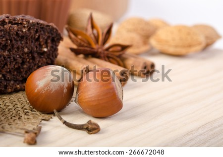 chocolate cake with nuts and cinnamon stick, star anise on wooden table - stock photo