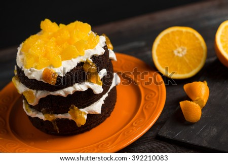 Chocolate cake with oranges on the wooden background