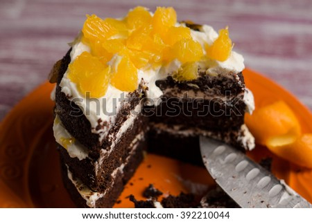 Chocolate cake with oranges on the wooden background. Selective focus.