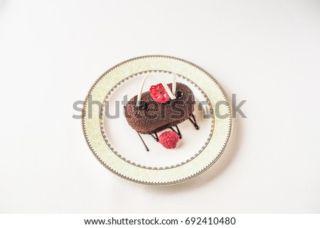 Chocolate cake with raspberries in a plate. Dessert on a white tablecloth. Delicious healthy fresh food.