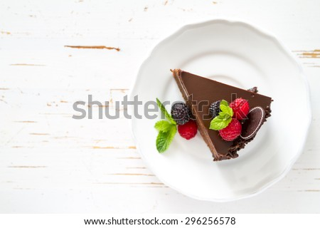 Chocolate cake with raspberry, blackberry, mint, white plate, white wood background, top view - stock photo