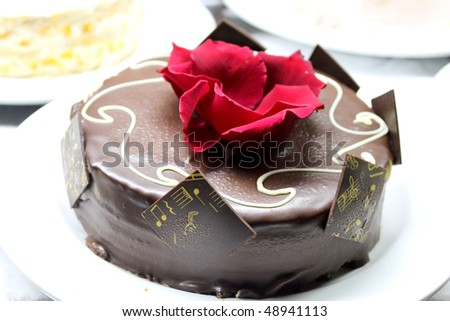 Chocolate cake with red flower - stock photo