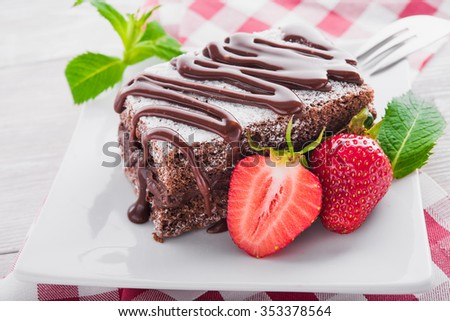 Chocolate cake with strawberries on the kitchen table